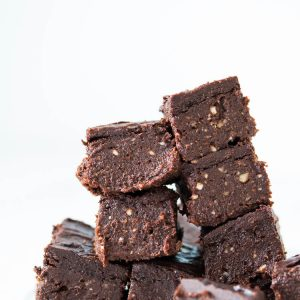 chocolate brownies with frosting stacked with a white backdrop
