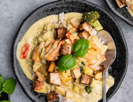 Green curry tofu in a black bowl with tofu and a basil leaf on top and a silver spoon on a grey backdrop