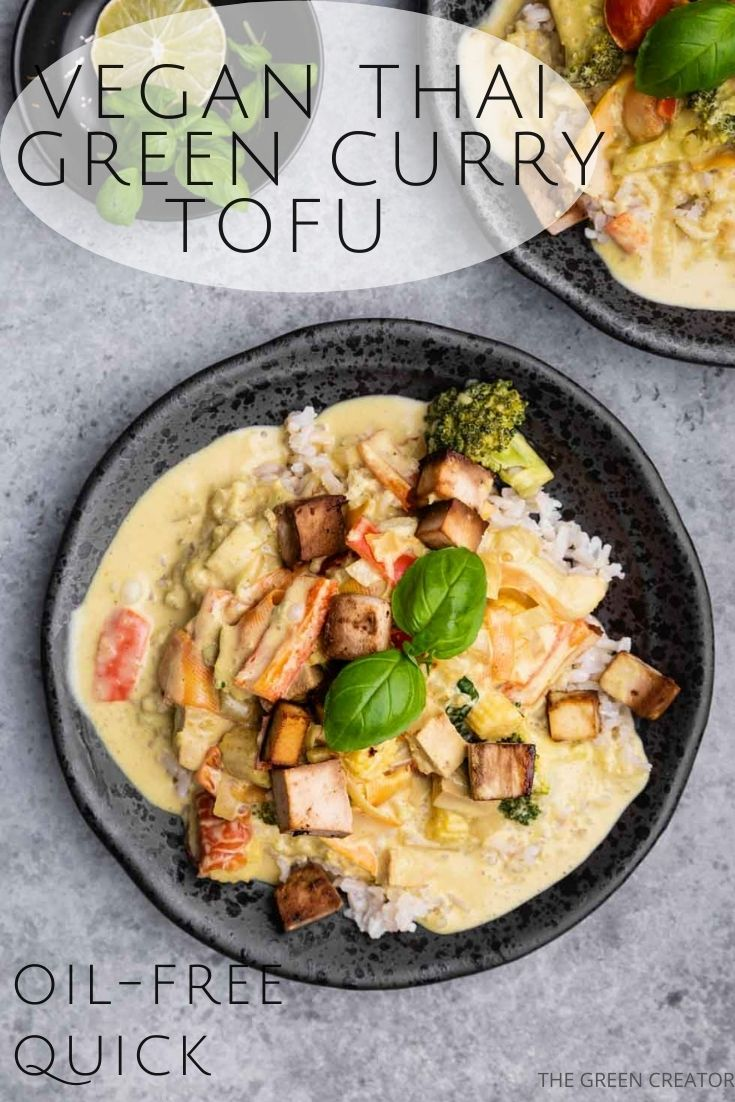 Green curry tofu in a black bowl with tofu and a basil leaf on top on a grey backdrop