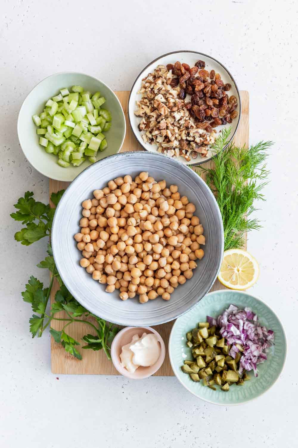 Ingredients for Chickpea Salad Sandwich on a wooden cutting board in bowls