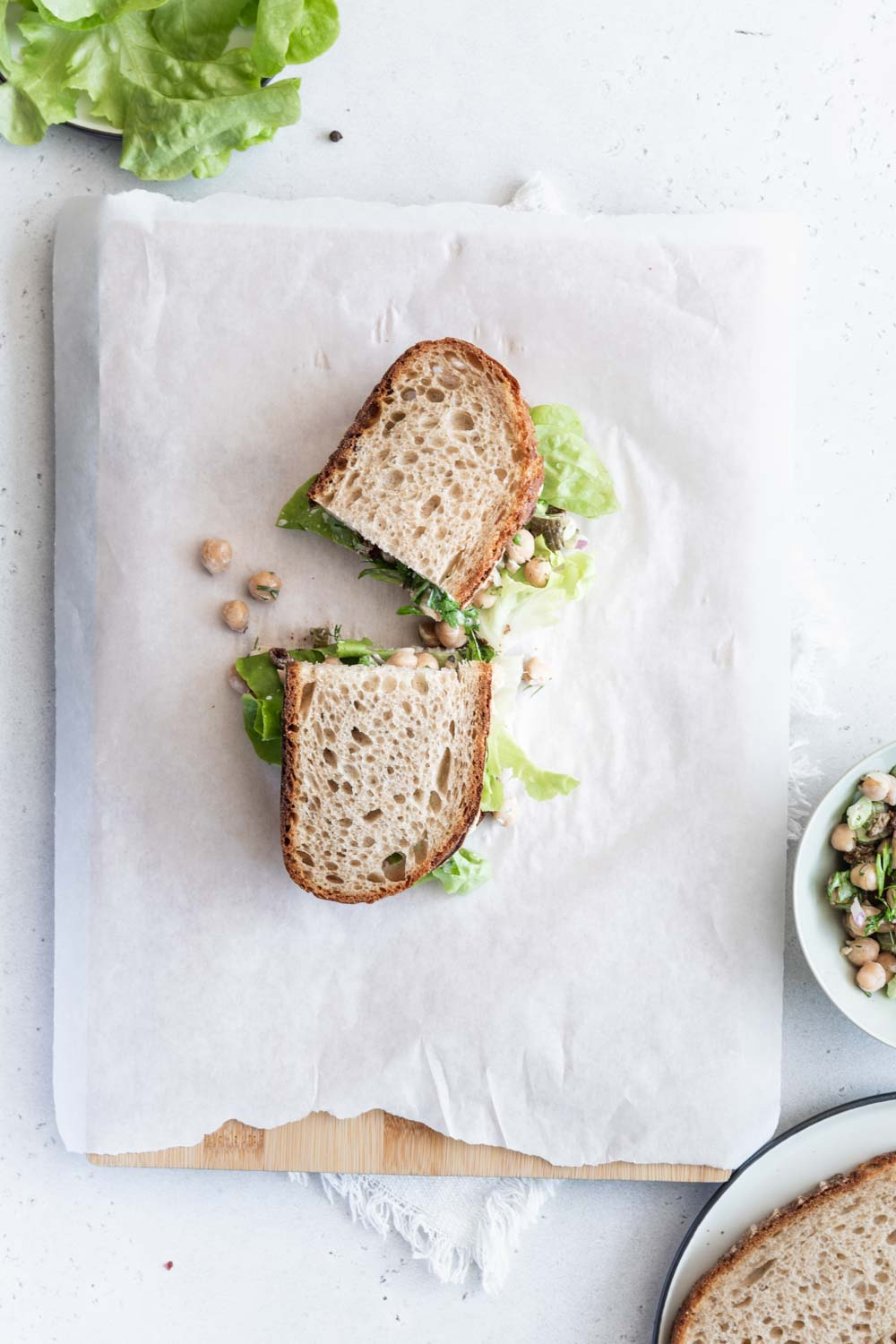 Chickpea Salad Sandwich in bread cut in half on white parchement paper