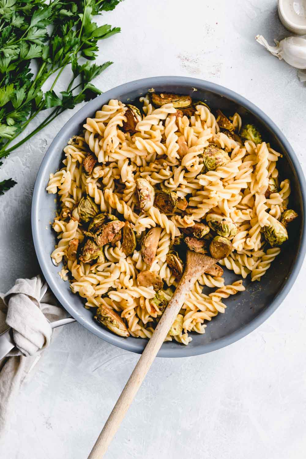Brussels sprout pasta in a blue pan with a wooden spoon on a white backdrop