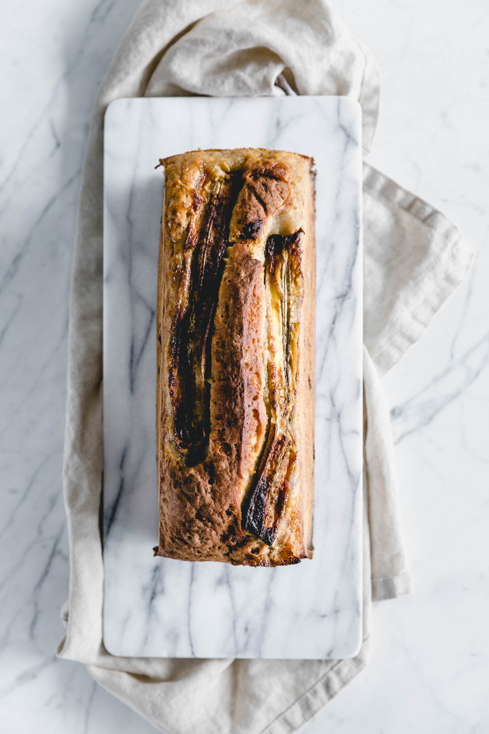 top view of whole banana bread with caramelized banana on top on white marble cutting board and light brown linen