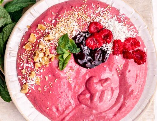 Raspberry Smoothie Bowl in a white bowl topped with mint leaves, nuts, jam and coconut flakes next to fresh mint leaves on a wooden backdrop