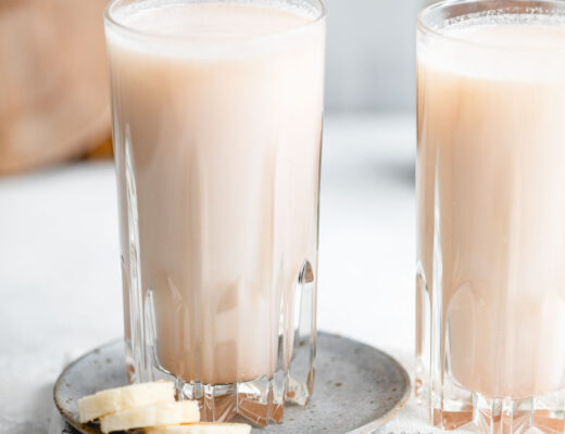 two tall glasses with banana bread milk on a white backdrop with a white napkin and a small light blue plate with a few slices of banana