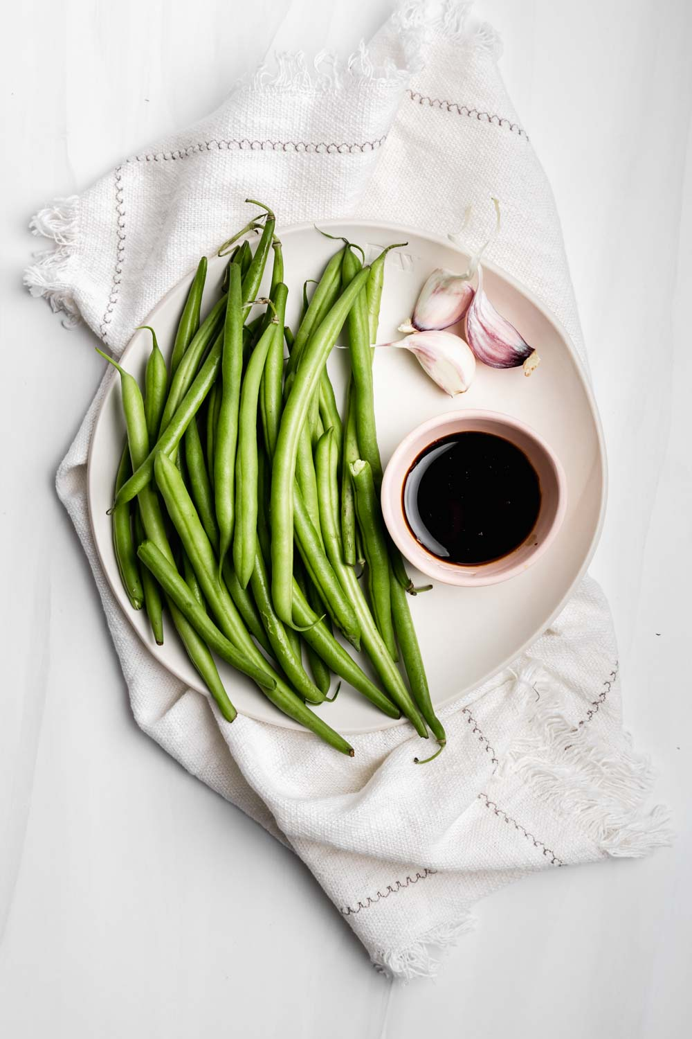 white plate with ingredients for making easy green beans recipe