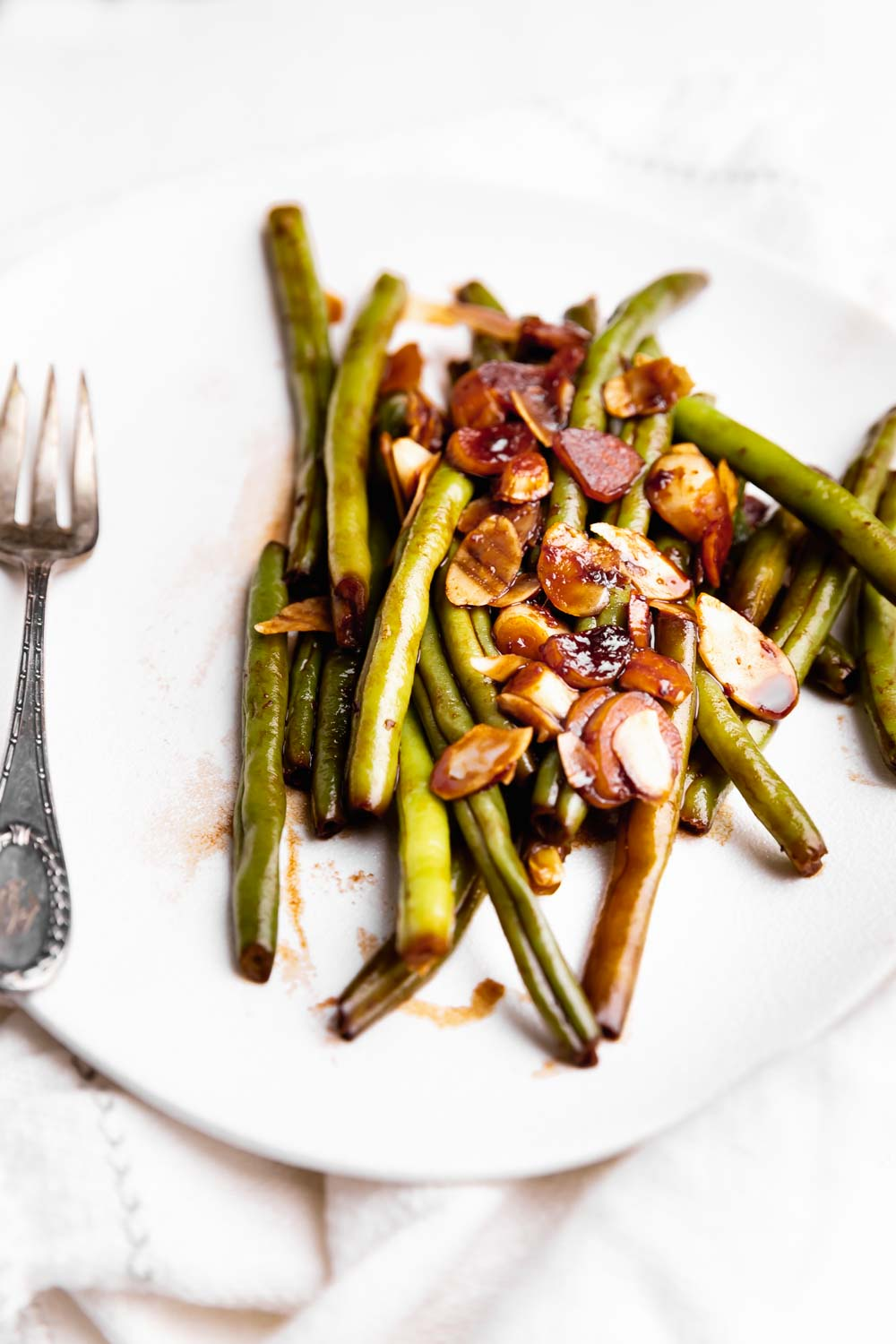 garlicky green beans on a white plate with a fork