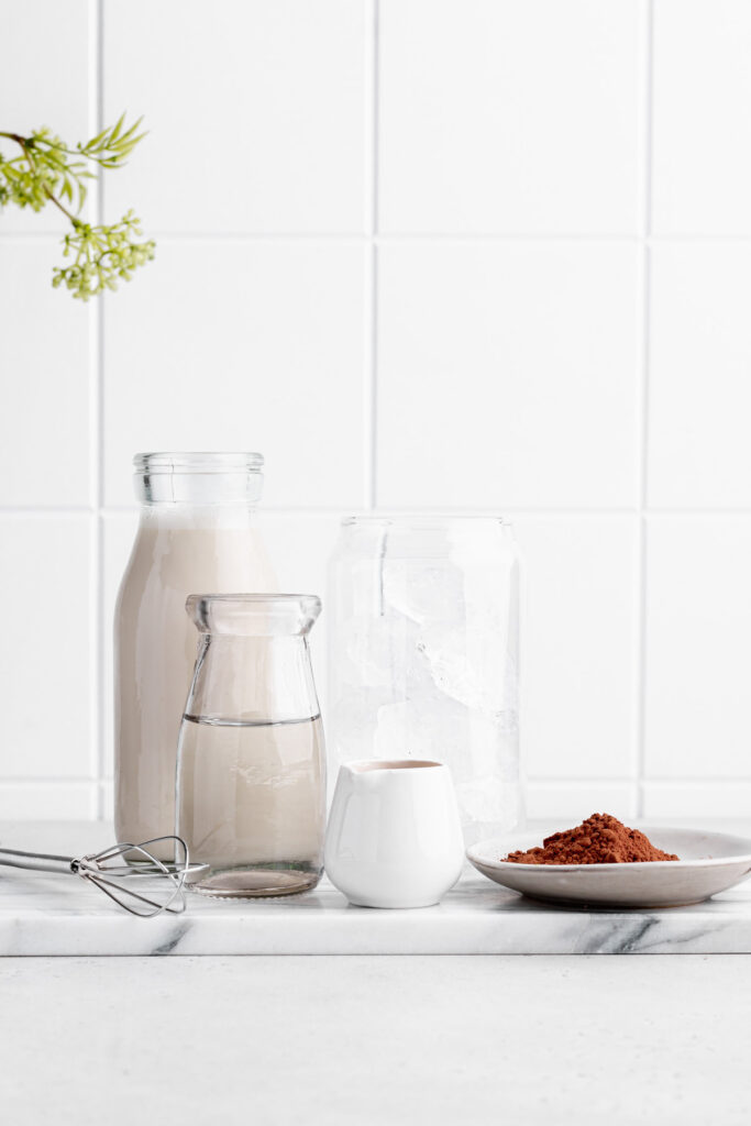 ingredients for iced chocolate on a white marble cutting board and a white tile backdrop