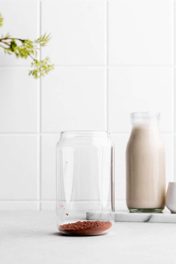 glass with cacao powder on a white backdrop with a bottle of oat milk in the back