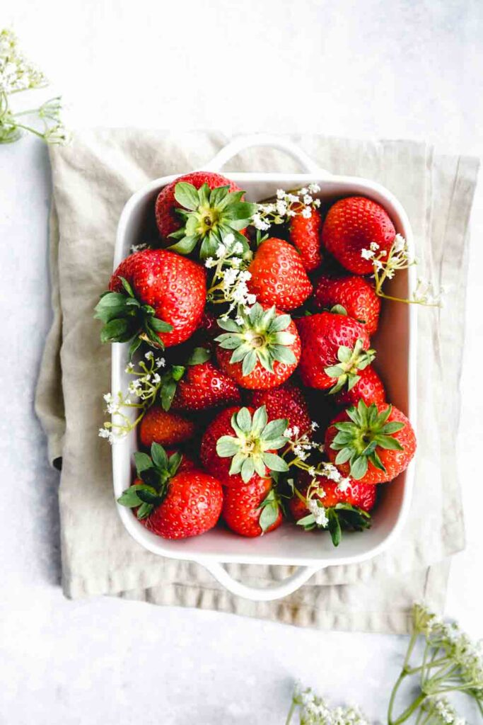 fresh strawberries with stem and little white flowers in a square white dish on a light brown napkin with a light backdrop