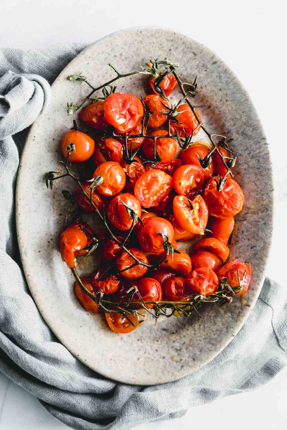 charred tomatoes in an oval plate with a light green napkin next to it on a white backdrop