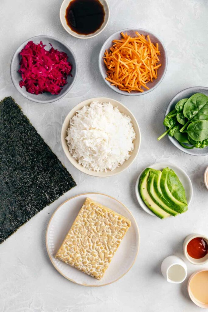 Ingredients for Onigirazu Rice Sushi Sandwiches on a white surface in small bowls