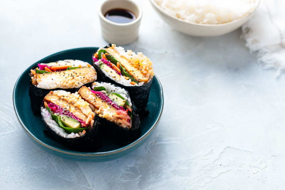 Four Onigirazu Rice Sushi Sandwiches on a white surface in a blue bowl with a bowl of rice in the background