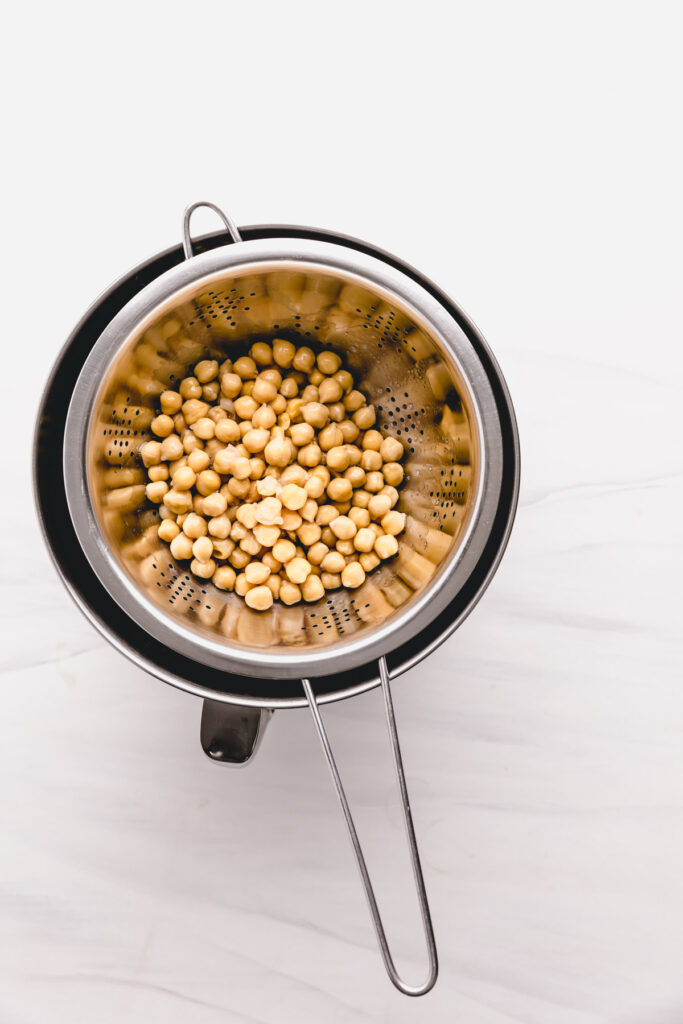 chickpeas in a stainless steel sieve on top of a stainless steel bowl on a white backdrop
