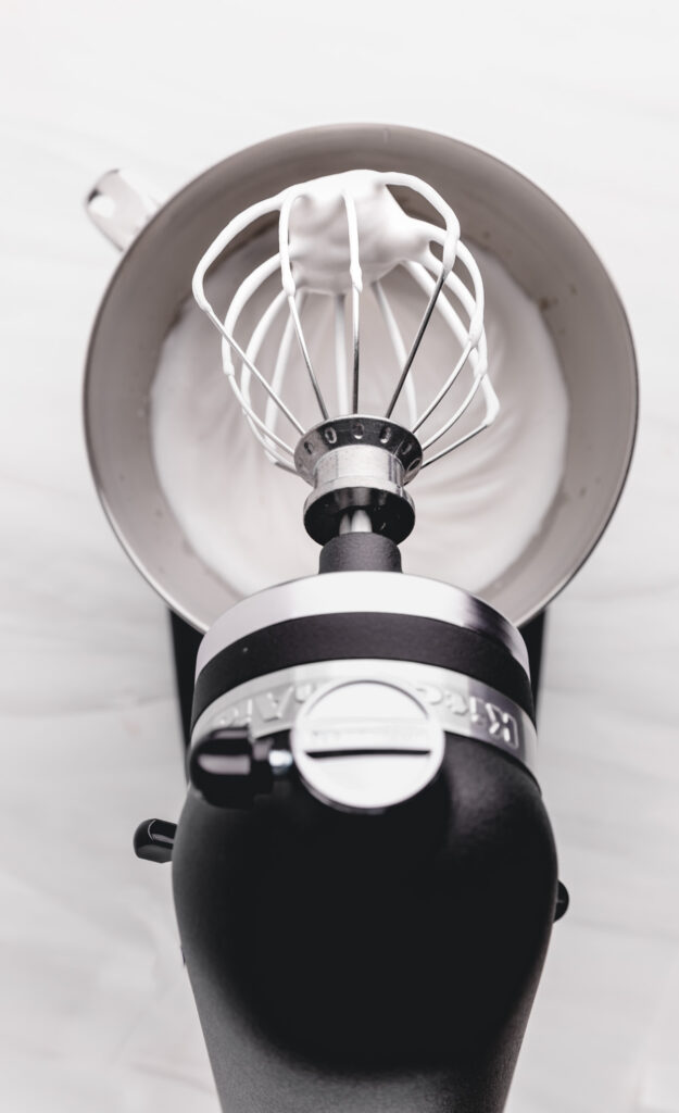 top view of a black kitchenaid mixer with aquafaba whipped cream in a stainless steel bowl