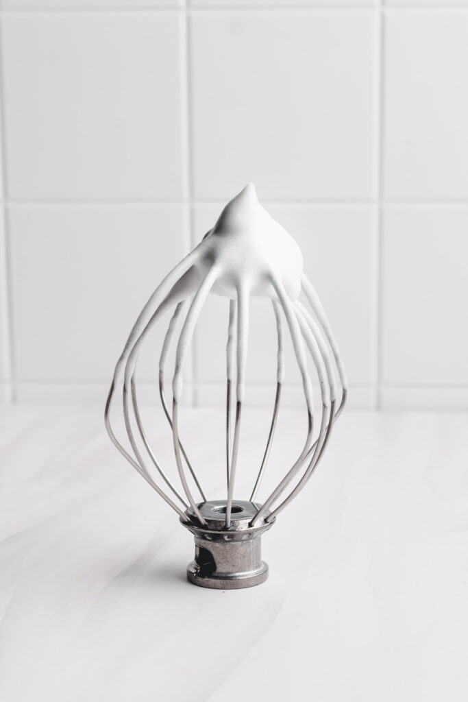 a whisk with whipped aquafaba with a white tile background