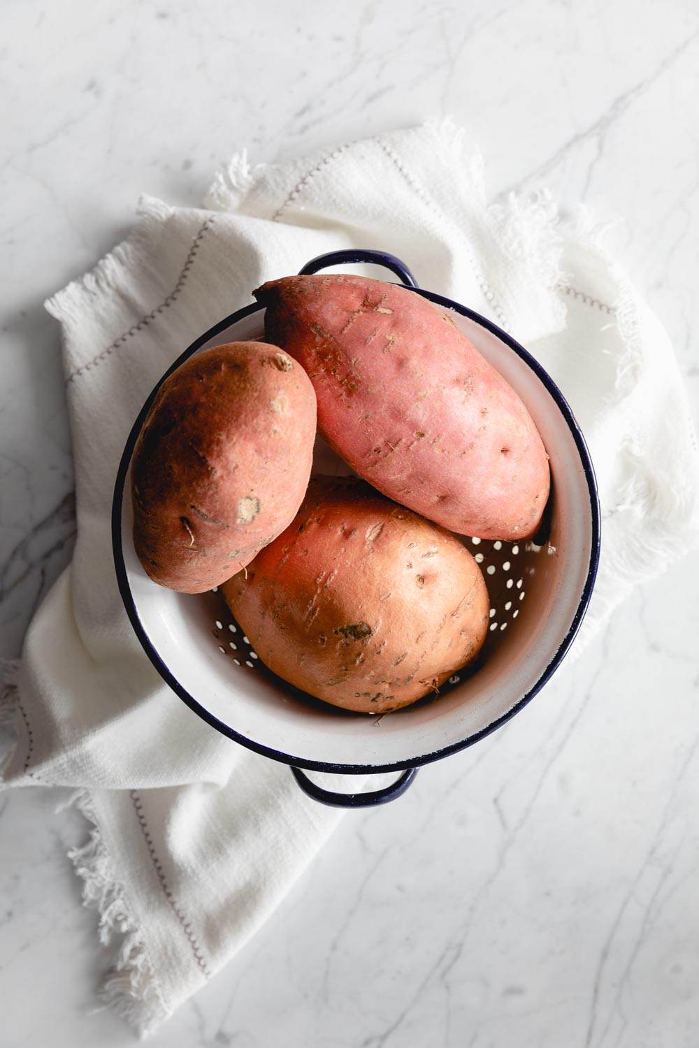 three sweet potato in a colander on a white napkin with a white backdrop