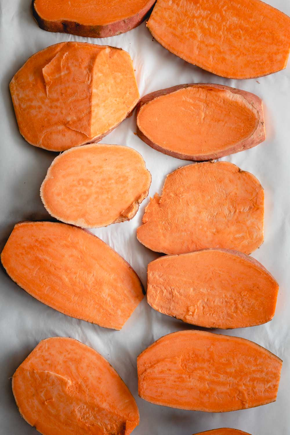 sliced raw sweet potato slices on a white paper