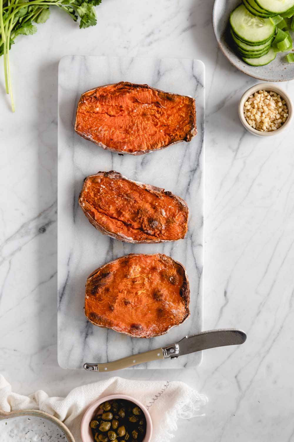 three sweet potato toasts from the oven without toppings on a marble cutting board with a small butterknife