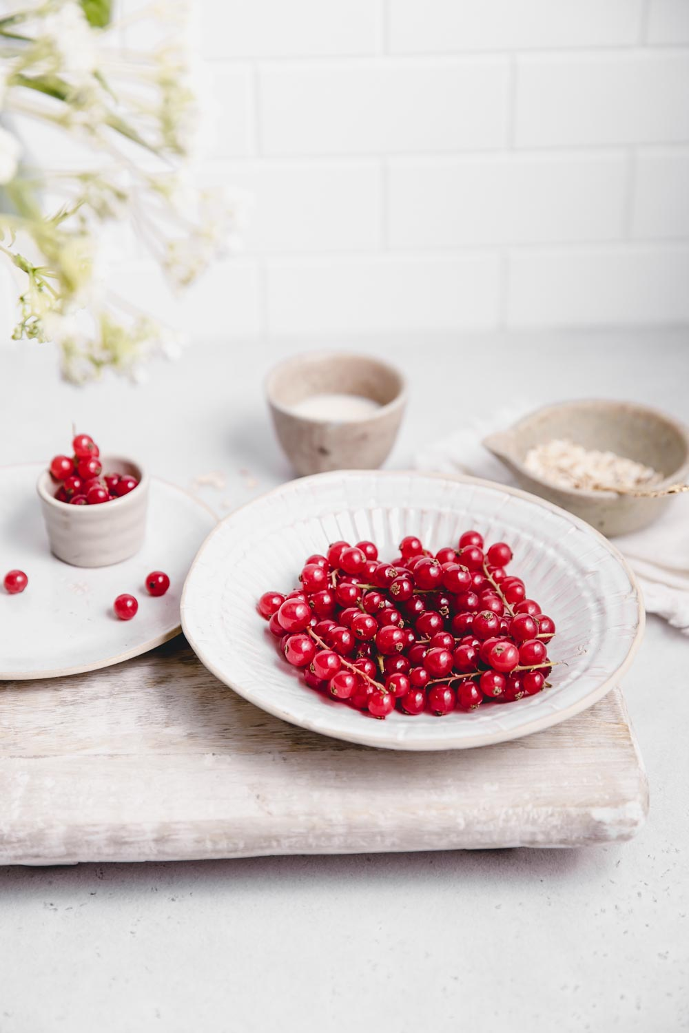 fresh red currants in a white bowl on a white backdrop with a white backdrop wall on a wooden chopping board next to a small bowl with red currants and a cup of oats and soy milk in the background