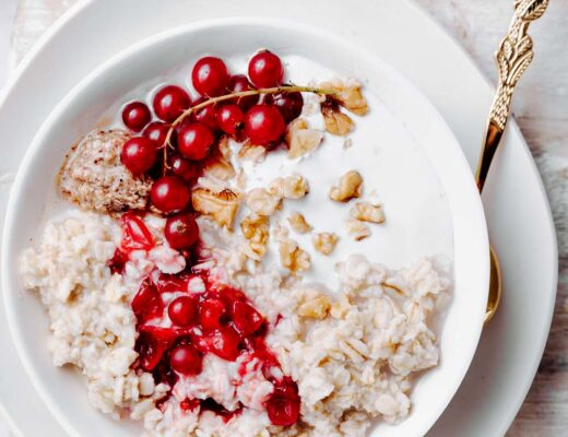 red currant oat porridge topped with red currant and chopped walnuts in a white bowl on a white plate on a light wooden cutting board with a golden spoon in the porridge