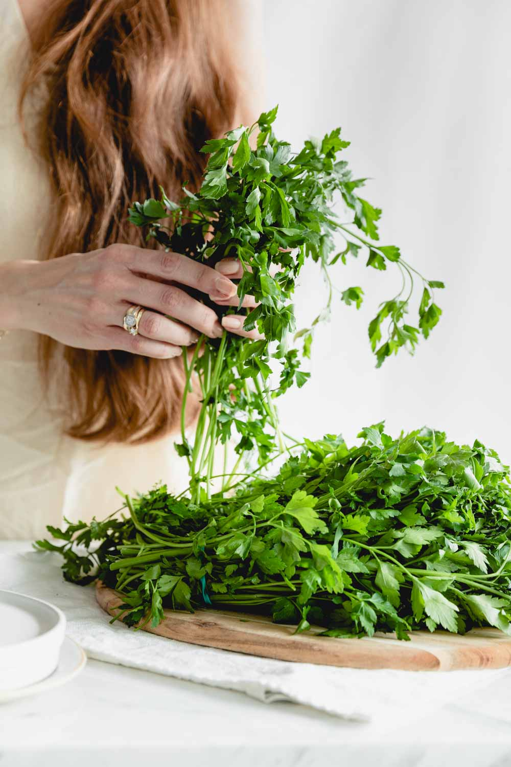 hands holding a bunch of parsley on a white backdrop with more herbs on a wooden cutting board