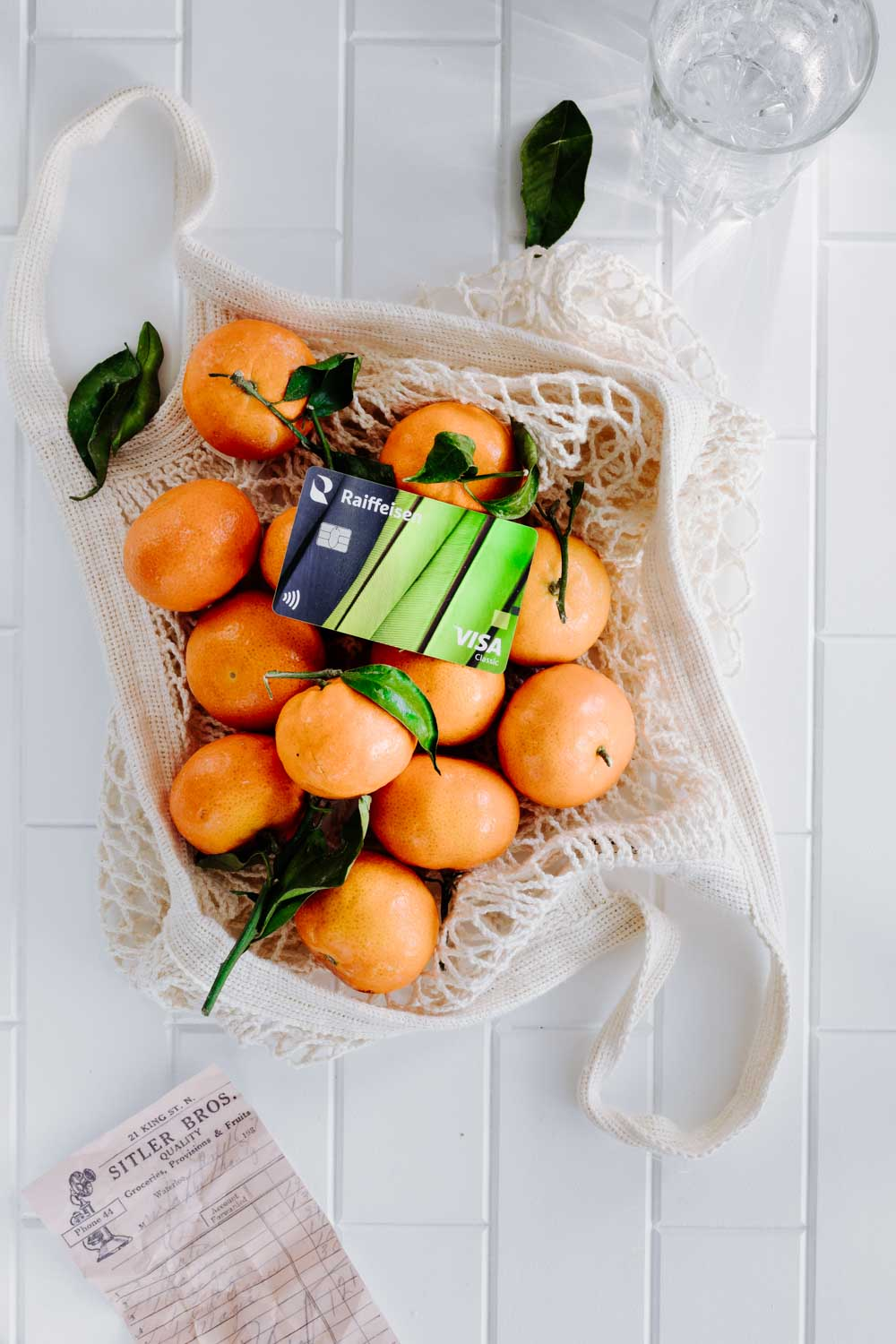 an open cotton shopping bag with mandarins and green leaves on a marble table with a bank card in the middle of the mandarins