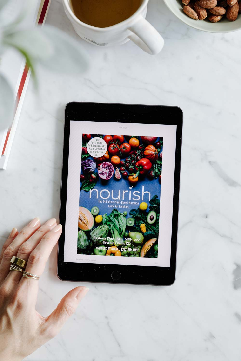 an ipad on a white marble table with a colorful book cover and a hand with rings next to it with a cup of tea, leaves and a bowl of almonds in the corner