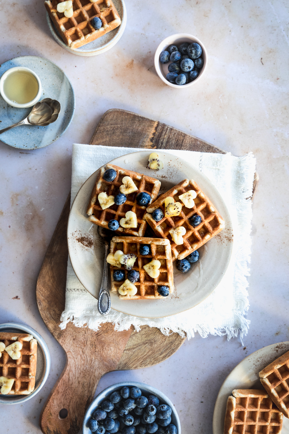 waffles on a plate on a white napkin on a wooden cutting board with a small bowl with syrup