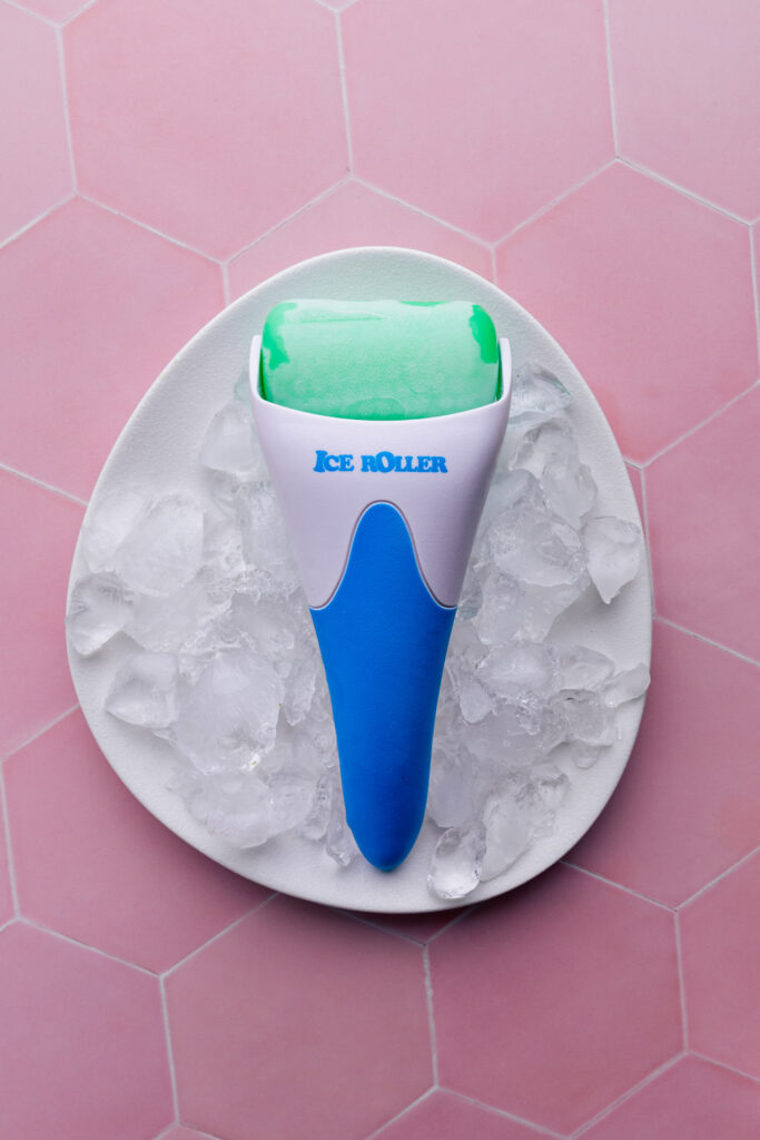 ice face roller on a white plate with ice cubes on a pink tile backdrop