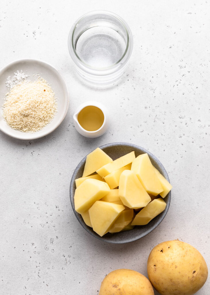 Ingredients for potato milk on a grey backdrop.