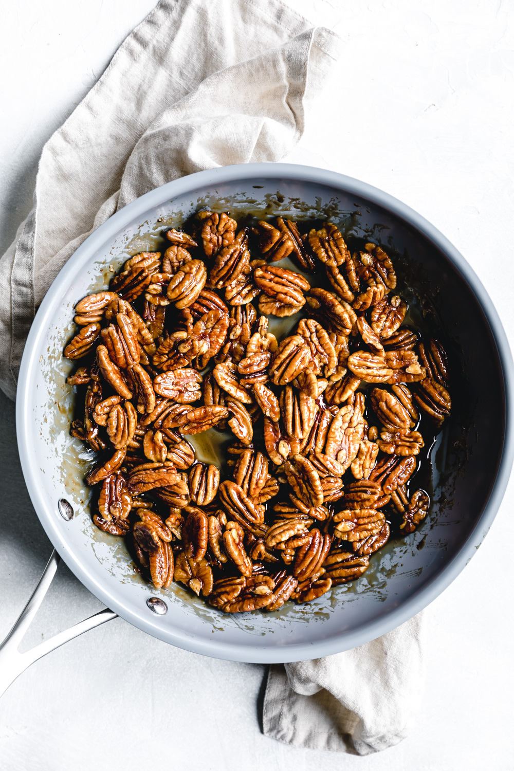sticky cooked candied pecans in blue skillet