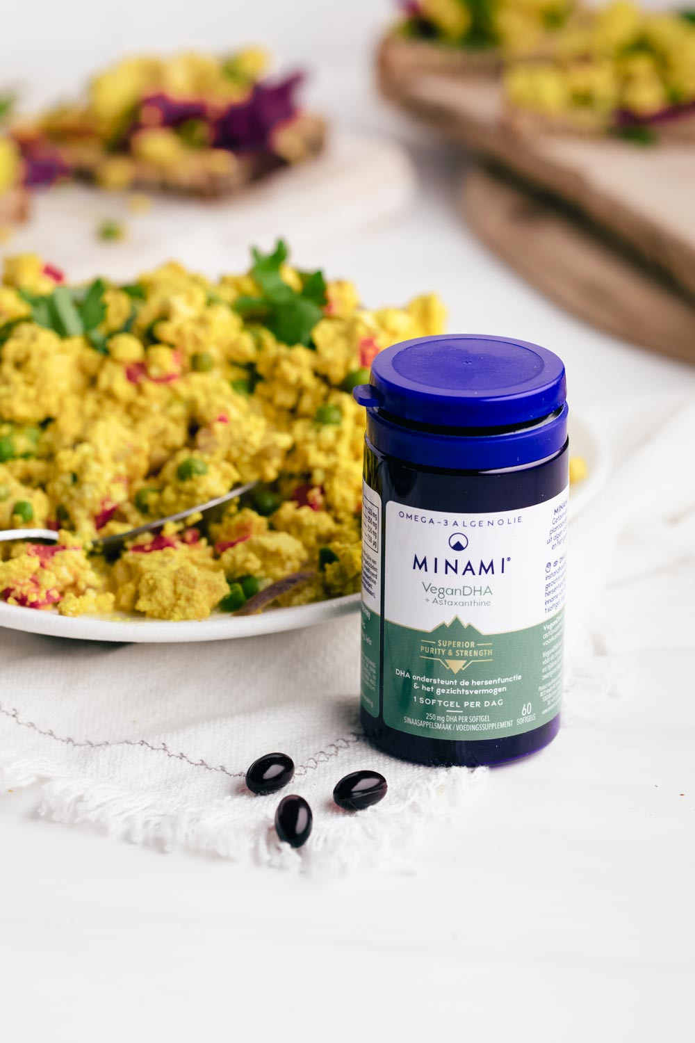 Omega 3 fatty acid supplement in a blue bottle on a white backdrop in front of scramble tofu.