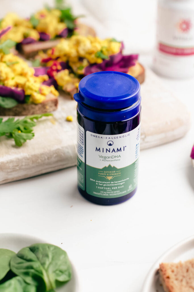 Blue bottle of Minami vegan DHA supplements with scrambled tofu sandwich in the background