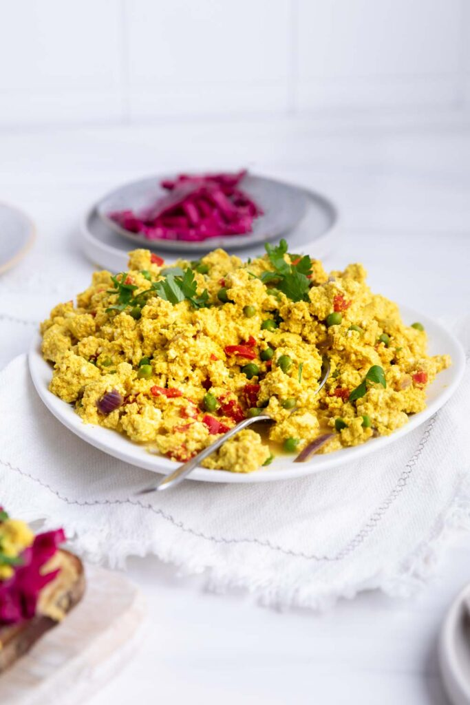 Scrambled tofu on a white plate with a spoon on a white napkin with a plate of pickled red cabbage in the background