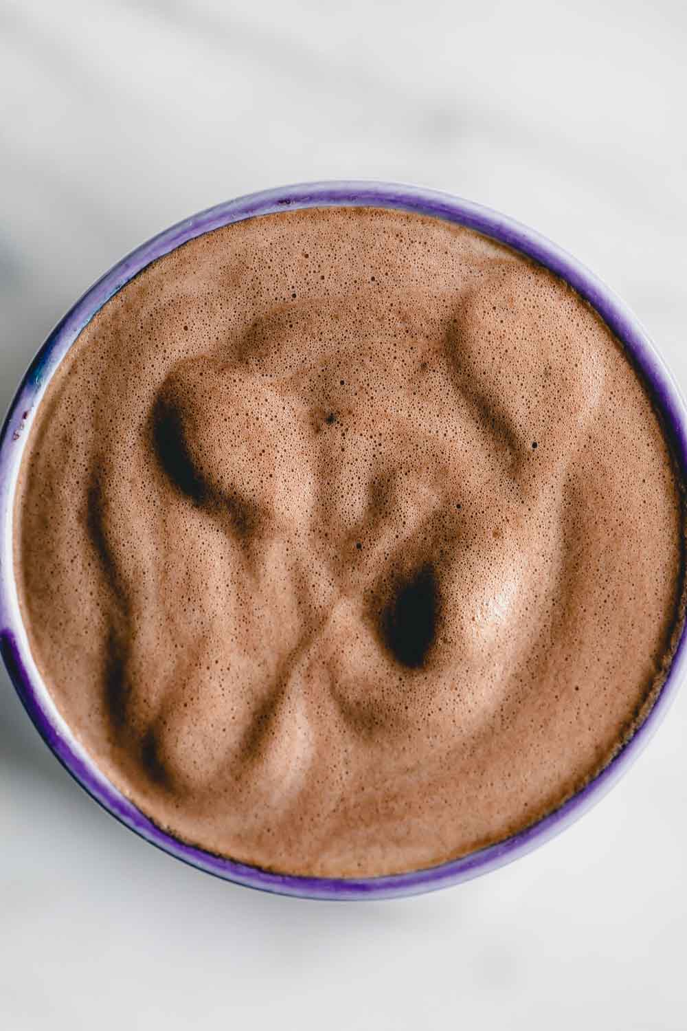 Frothed vegan chocolate milk in a mug with a blue edge