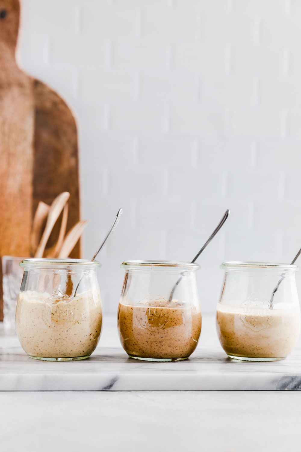 Three quinoa summer salad dressings next to eachother in small glass jars with a teaspoon on white marble and a light background with a wooden cutting board and wooden utensils in the background.