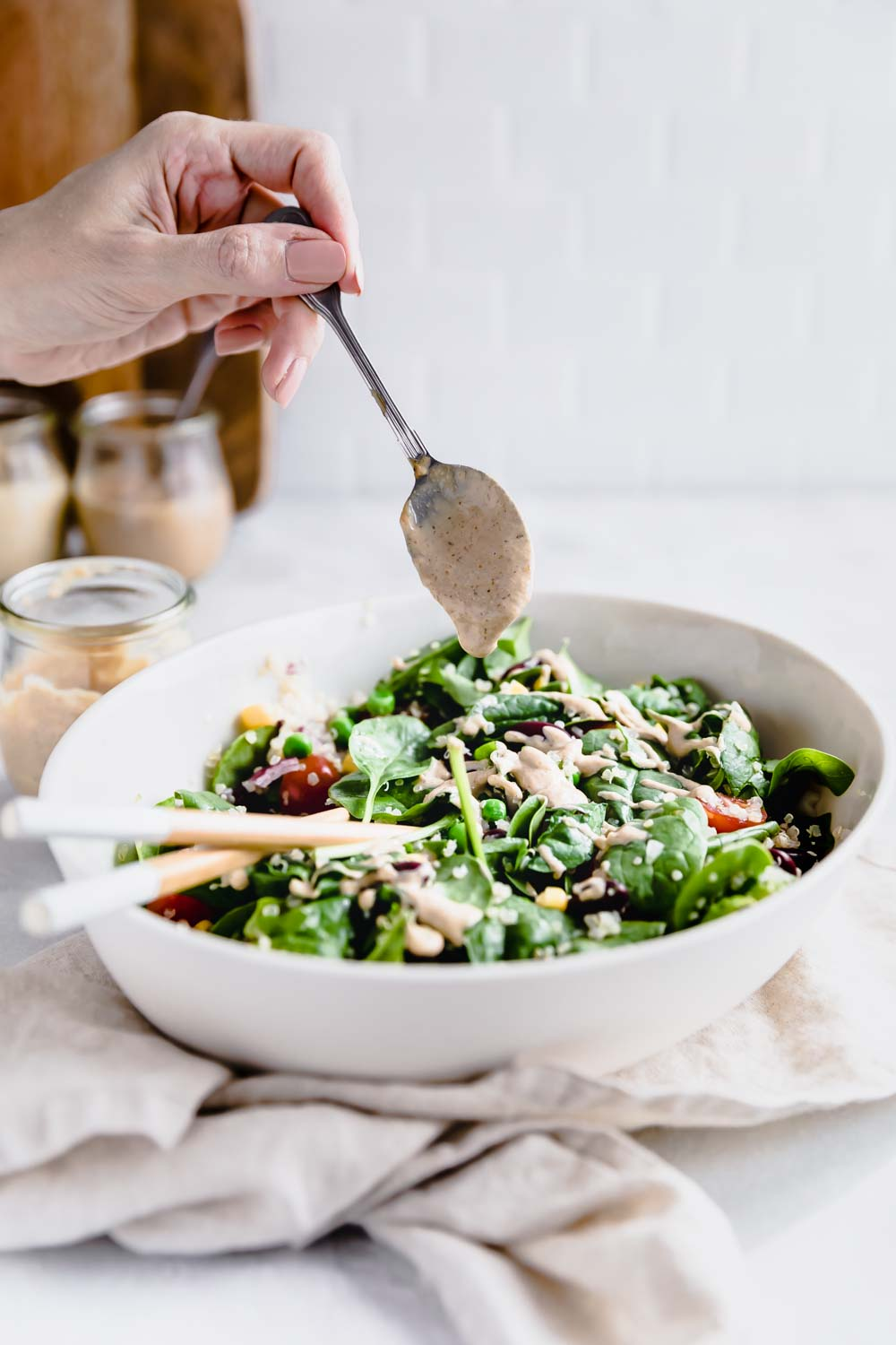 Quinoa salad in an oval bowl with chopstick on a lightbrown napkin and a light backdrop and a hand pouring a dressing in the salad with a teaspoon.
