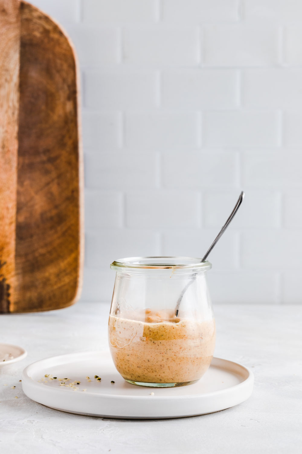 Miso dressing in a small glass jar with a teaspoon on a light backdrop with a wooden cutting board and wooden utensils in the background.