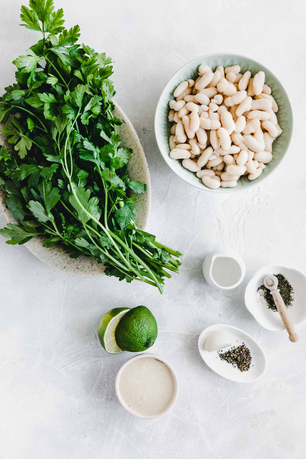 ingredients for white bean dip on a light backdrop