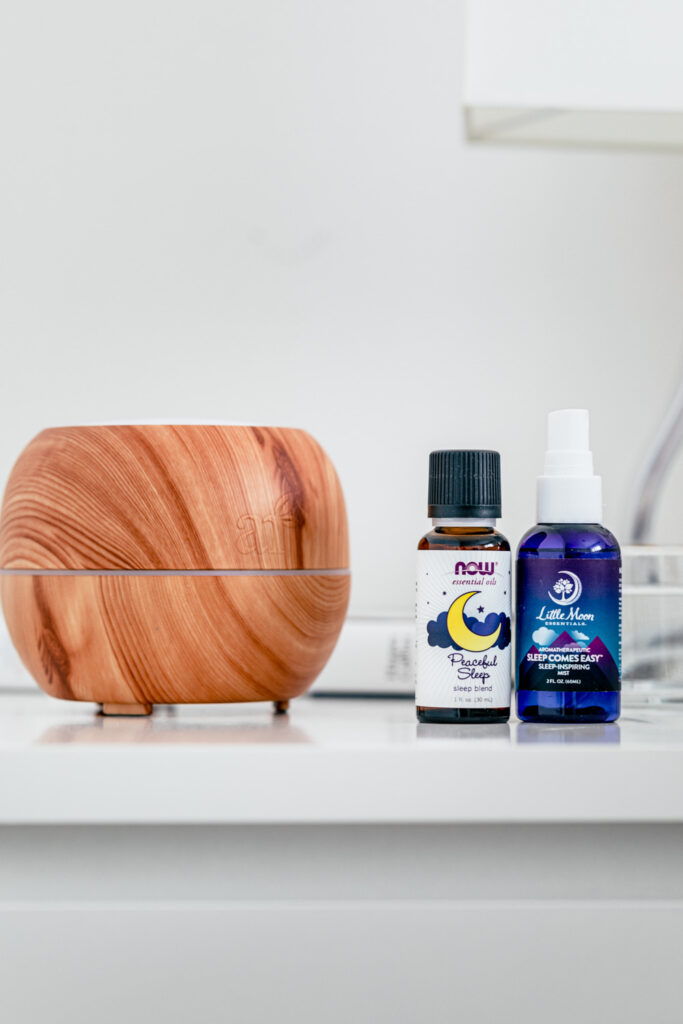a wood colored diffuser on a white side table with two blue bottles of essential oil and sleep mist next to it