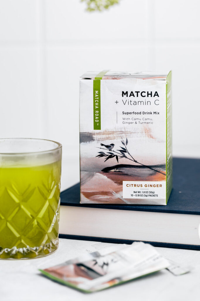 a box with matcha on a blue book with a white backdrop and a glass with macha next to it