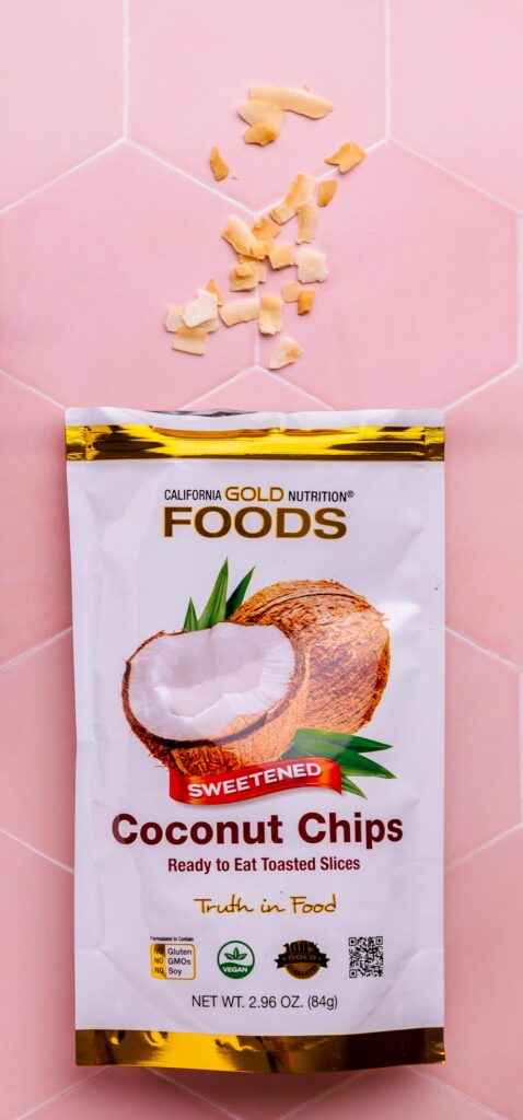 a bag open flat with shredded coconut in front of it on a pink tile backdrop