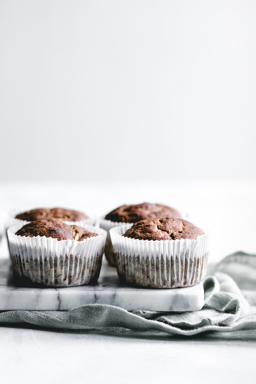 Zucchini Muffins in white muffin mold on a marble cutting board on a a green napkin