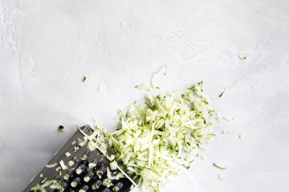 grated zucchini on white backdrop