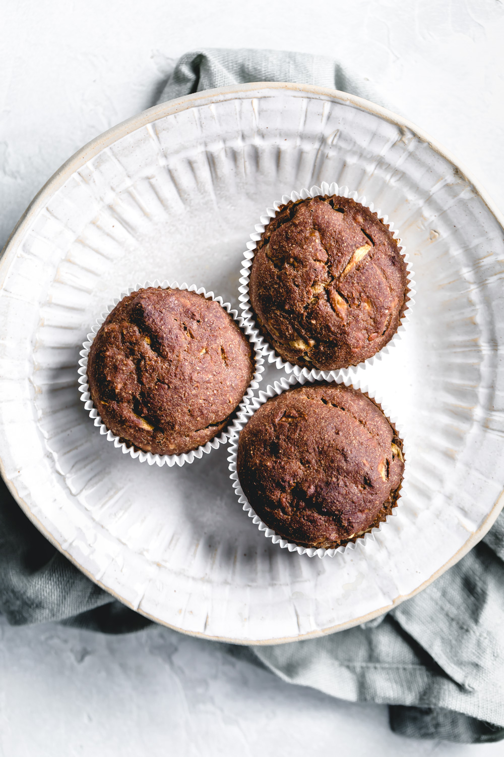 Zucchini Muffins in white muffin molds in a white bowl