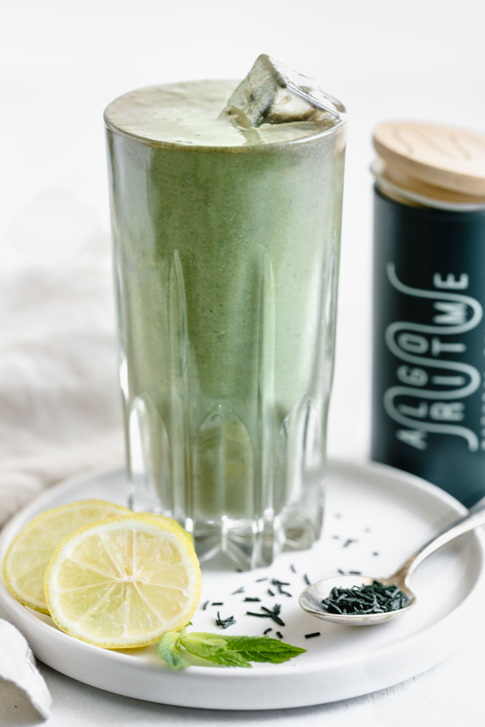 green smoothie in tall glass with ice cubes on white plate with a spoon with spirulina, lemon slices and mint leaves