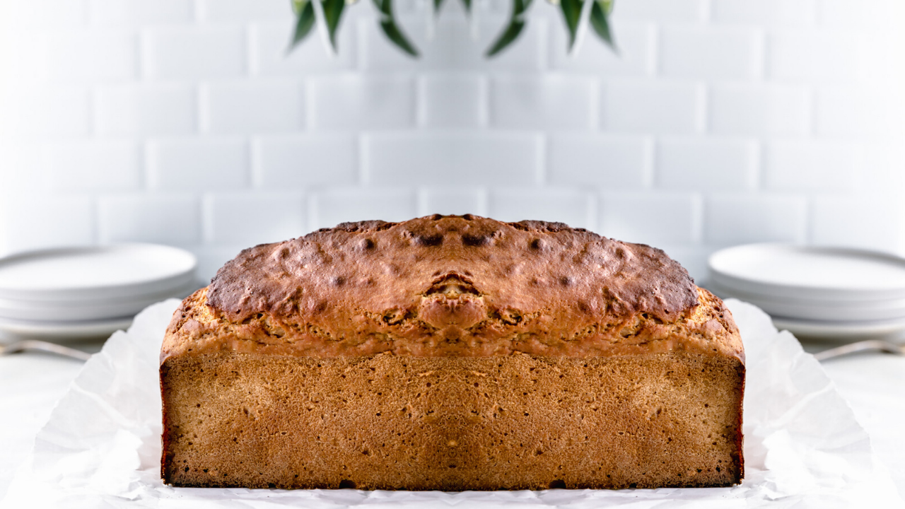 whole baked applesauce bread with a white tile kitchen background