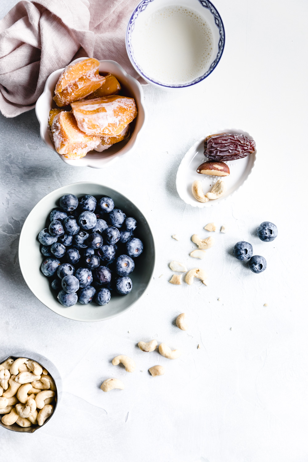 ingredients for blueberry smoothie in bowls and glasses on a white backdrop with a pink napkin
