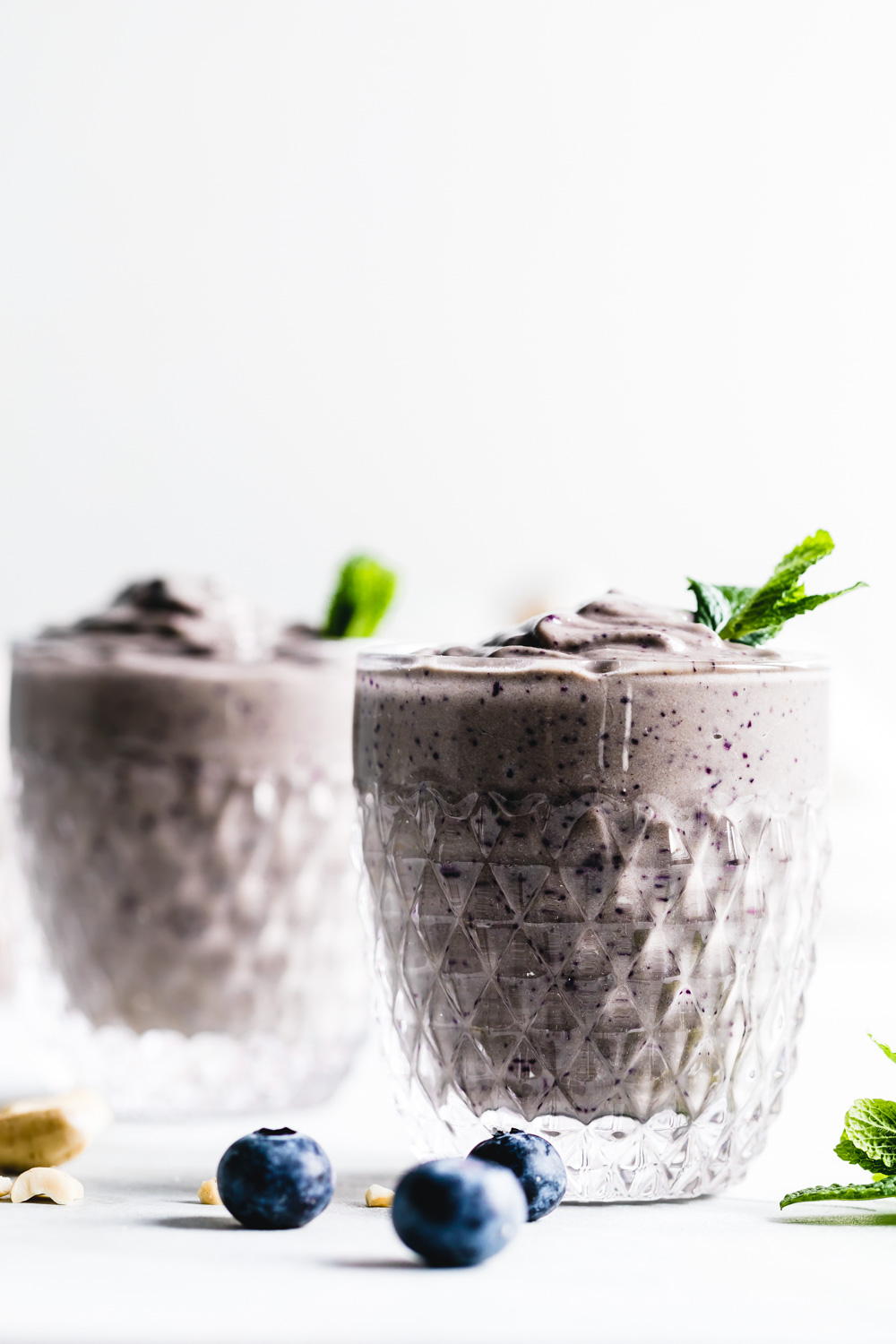 two glasses with blueberry smoothie in a small glass topped with mint leaves on a white marble cuttingboard with a white backdrop and a few blueberries